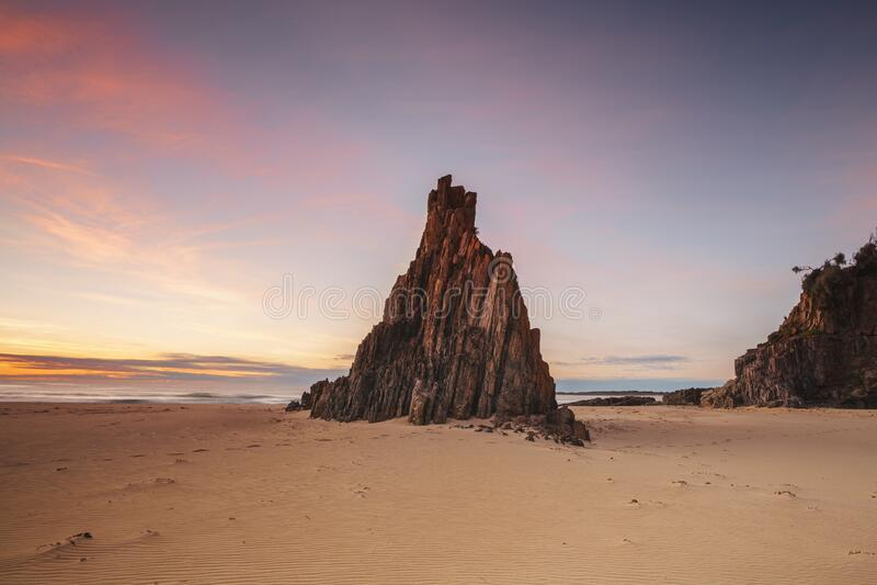 Pilha de pirâmide na praia com belos céus do sol com nuvens vermelhas fotografia de stock royalty free