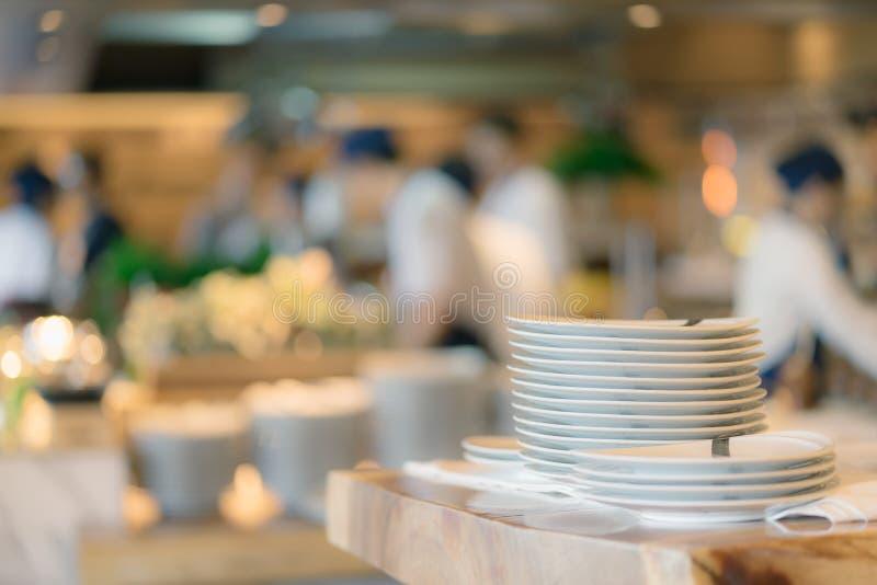 Pilha de placa no fundo contrário e borrado Grupos de contador da preparação do cozinheiro chefe do alimento na cozinha aberta, i foto de stock