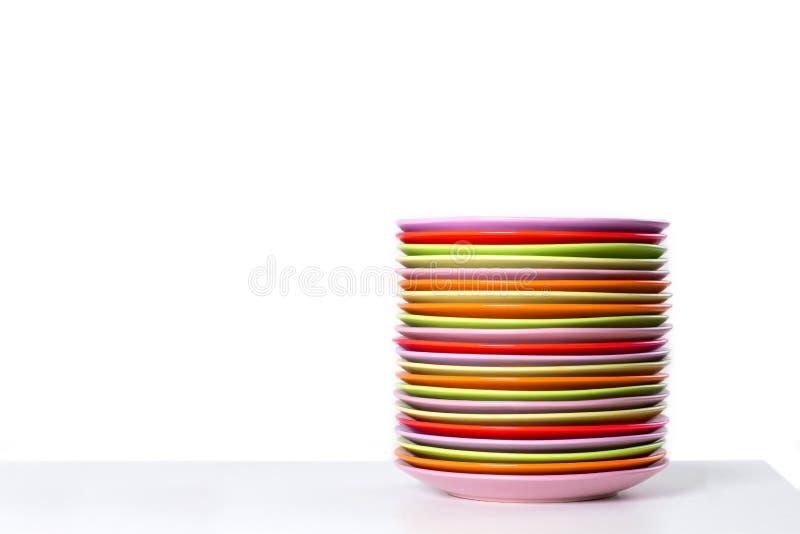 A pilha de placas da cor em uma tabela foto de stock
