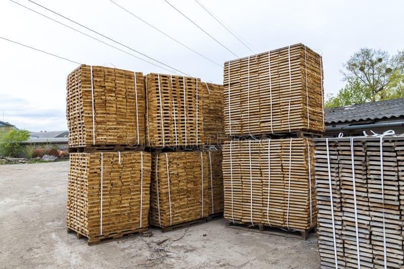 Pilha de placas de madeira e de parafusos prisioneiros novos na jarda de madeira serrada De madeira imagens de stock royalty free