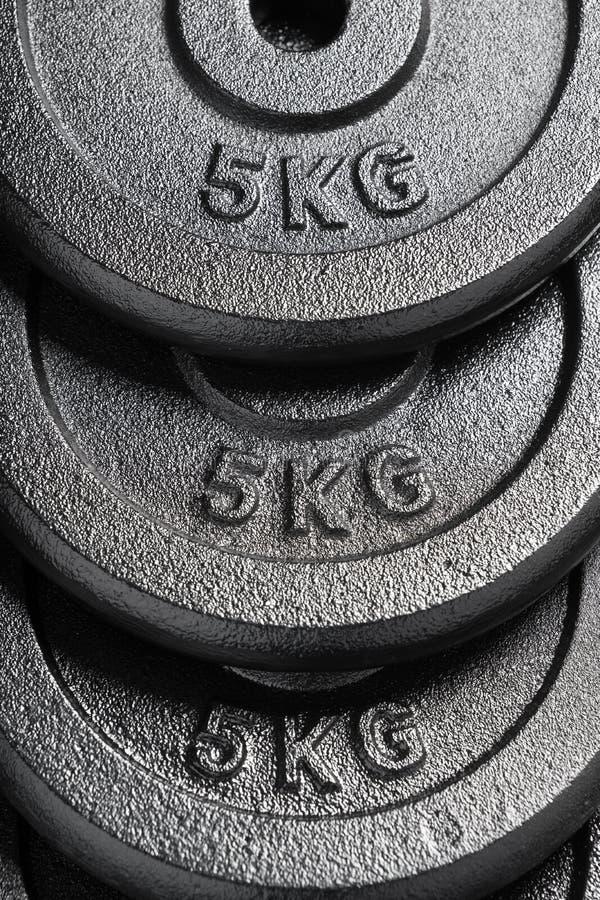 Pilha de placas do peso do barbell/peso dentro de um gym do halterofilismo imagem de stock royalty free