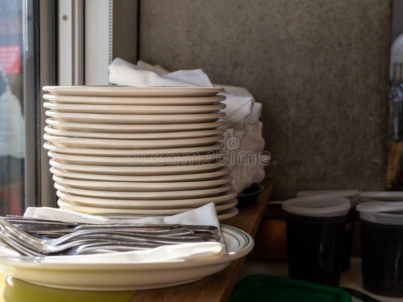 Pilha de placas e utensílios e recipientes dos molhos foto de stock