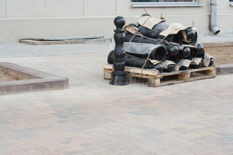A pilha de postes de amarração do estacionamento e do controlo de tráfico em uma pálete deve ser instalada na rua imagens de stock royalty free