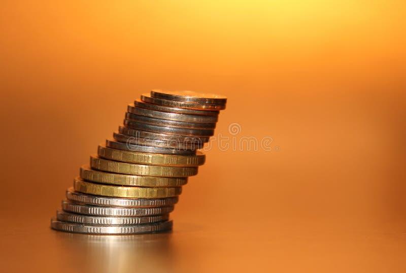 Pilha de queda de moedas em um fundo dourado fotografia de stock royalty free