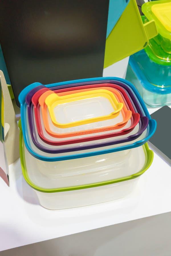 Pilha de recipientes plásticos com tamanhos e cores diferentes da tampa imagem de stock