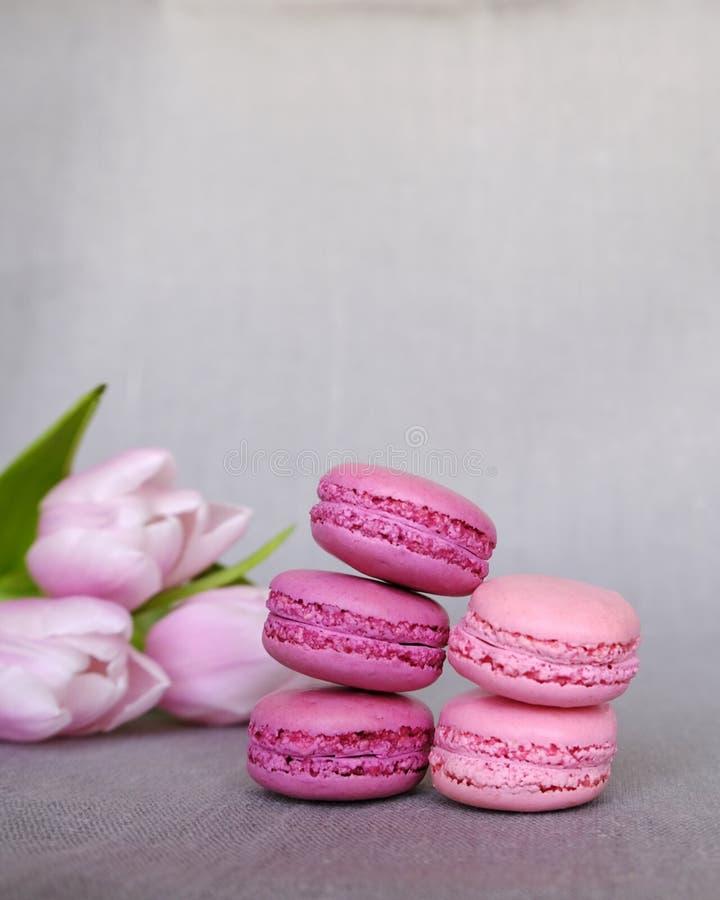 Pilha de rosa e de tulipas francesas roxas dos macarons e da florescência no fundo cinzento Espa?o para o texto fotografia de stock