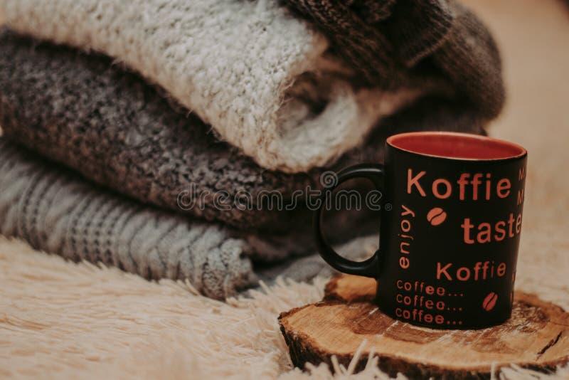 Pilha de roupa feita malha acolhedor em um tapete macio Caneca em um suporte de madeira foto de stock royalty free