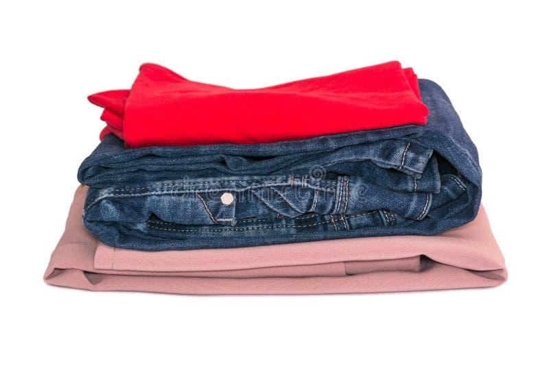 Pilha de roupa isolada no fundo branco Blusa das calças de brim, a vermelha e a bege fotos de stock