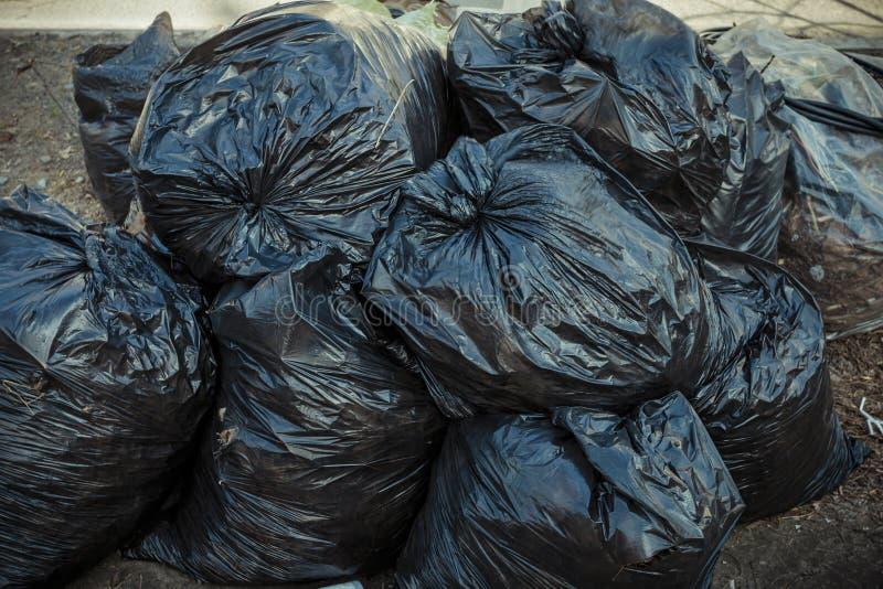 Pilha de sacos de lixo pretos no passeio fotos de stock royalty free