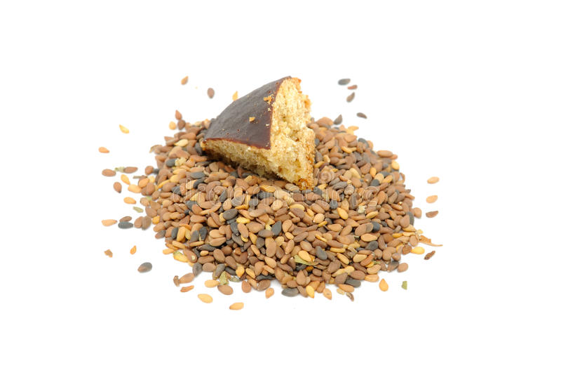 Pilha de sementes do sésamo de Tan com parte de bolinho fotos de stock royalty free