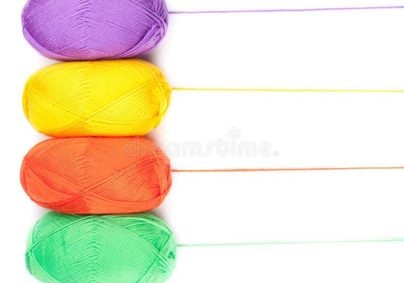 Pilha de skeins do fio em cores amarelas, alaranjadas, verdes, roxas fotos de stock