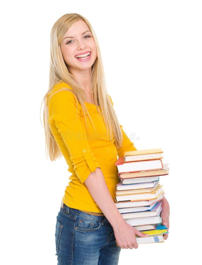 Pilha de sorriso da terra arrendada da menina do estudante de livros foto de stock royalty free