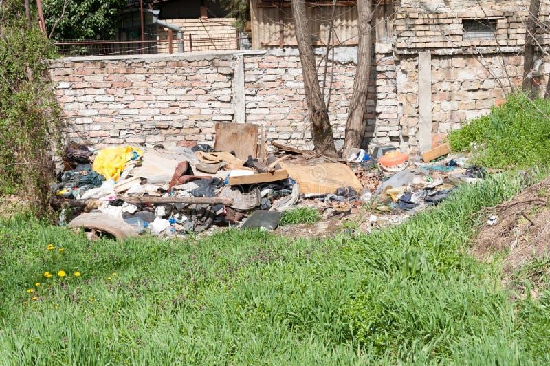A pilha de sucata e de lixo despejou na natureza ou no parque na cidade que polui o ambiente com cheiro mau fotografia de stock royalty free