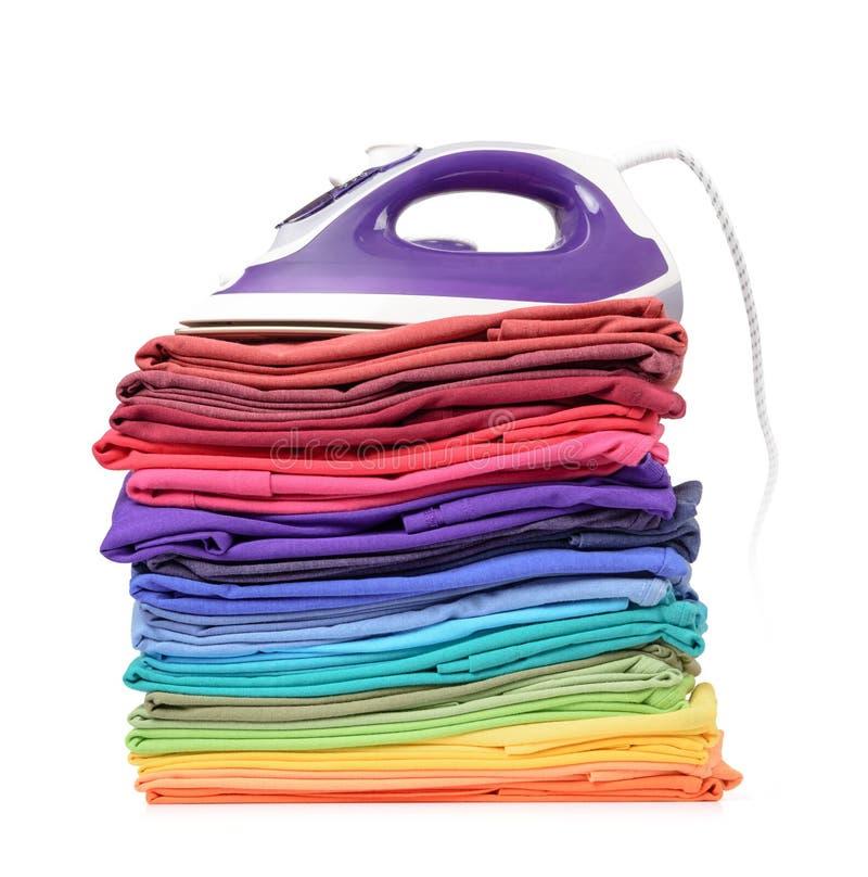 Pilha de t-shirt coloridos e a parte superior do ferro, isolada no fundo branco O arquivo contem um trajeto à isolação fotos de stock royalty free