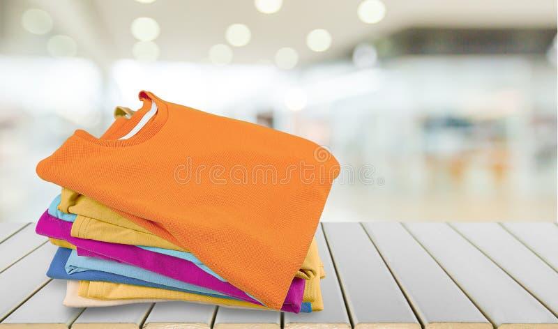 Pilha de t-shirt coloridos na tabela de madeira imagem de stock royalty free