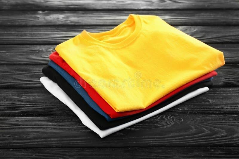 Pilha de t-shirt coloridos no fundo de madeira foto de stock