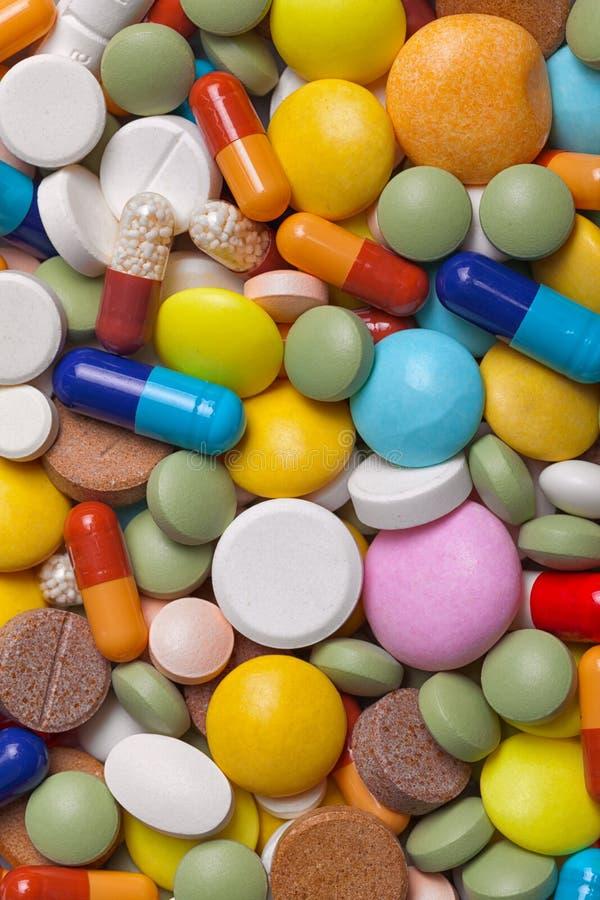 Pilha de tabuletas coloridas das medicamentações - fundo médico foto de stock