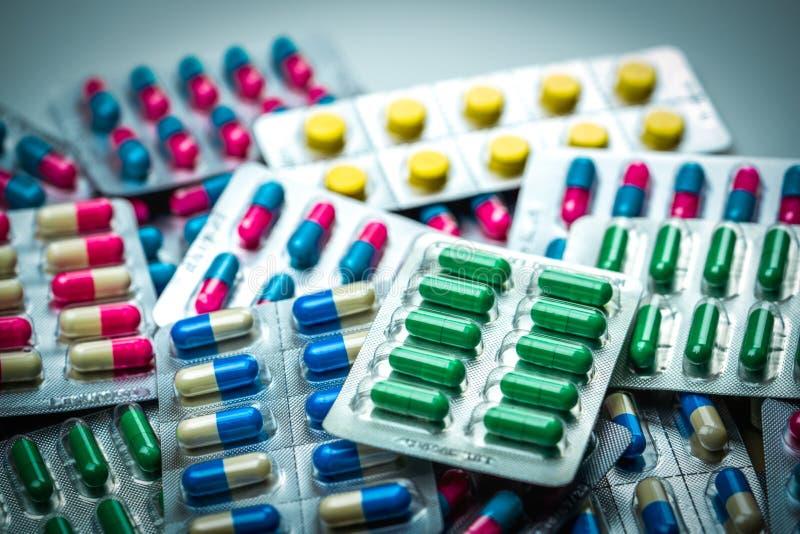 Pilha de tabuletas e de comprimidos coloridos das cápsulas em blocos de bolha Gl fotos de stock royalty free