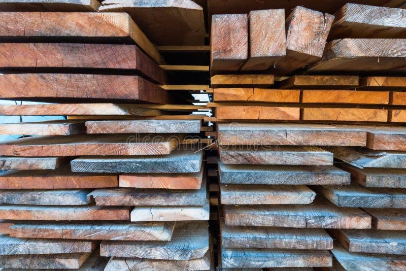 A pilha de tamanho diferente cortou as pranchas de madeira para o constructio de construção foto de stock