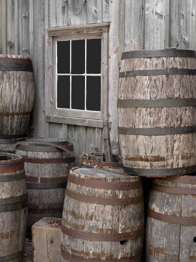 Pilha de tambores de madeira velhos por uma parede. fotos de stock royalty free