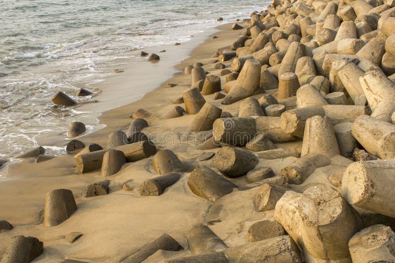 a pilha de tetrapods concretos cinzentos projeta-se da areia amarela molhada Barreira do tsunami fotos de stock royalty free