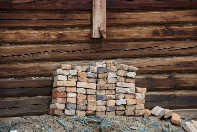 Pilha de tijolos velhos na parede do fundo uma casa de madeira imagem de stock royalty free