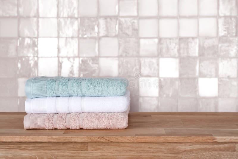 Pilha de toalha de banho na superf?cie de madeira antes da parede do azulejo fotografia de stock royalty free