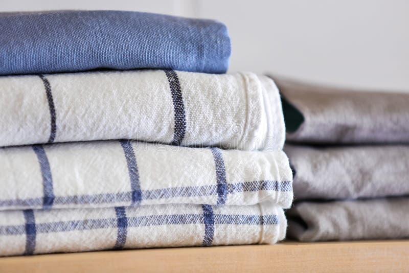 Pilha de toalhas de cozinha limpas na prateleira de madeira, close up fotos de stock