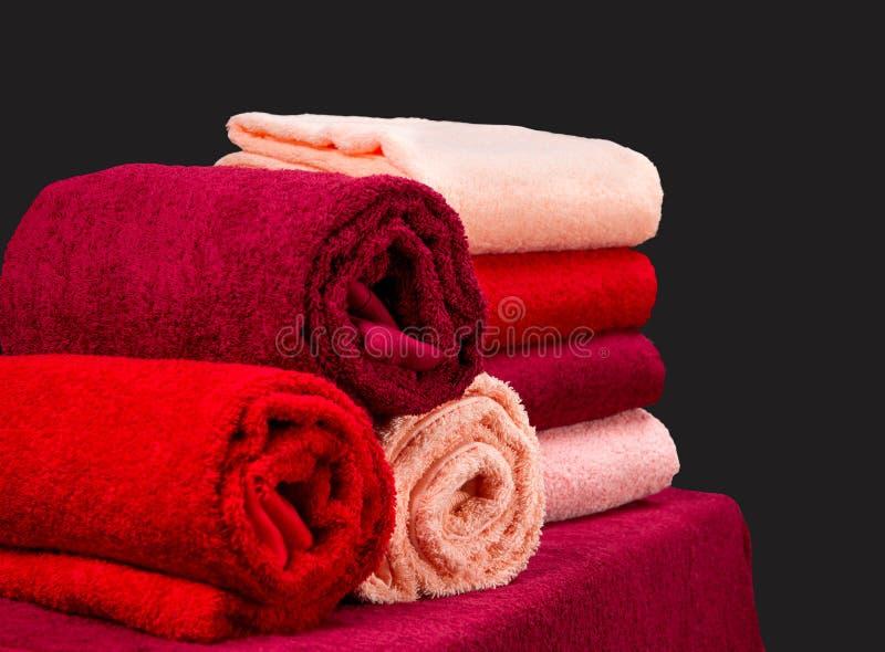 Pilha de toalhas de terry coloridas em uma tabela no fundo escuro imagens de stock