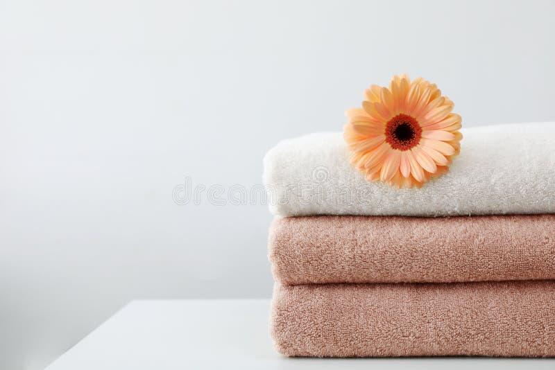 Pilha de toalhas frescas com a flor na tabela contra o fundo branco fotos de stock royalty free