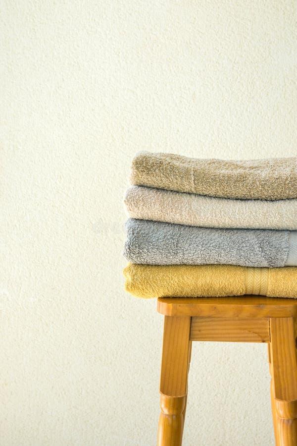 Pilha de toalhas de terry dobradas limpas no fundo branco da parede do tamborete alto de madeira Conceito da limpeza do bem-estar foto de stock