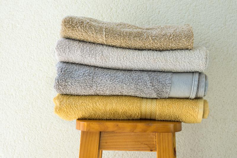 Pilha de toalhas de terry dobradas limpas no fundo branco da parede do tamborete alto de madeira Conceito da limpeza do bem-estar imagem de stock royalty free