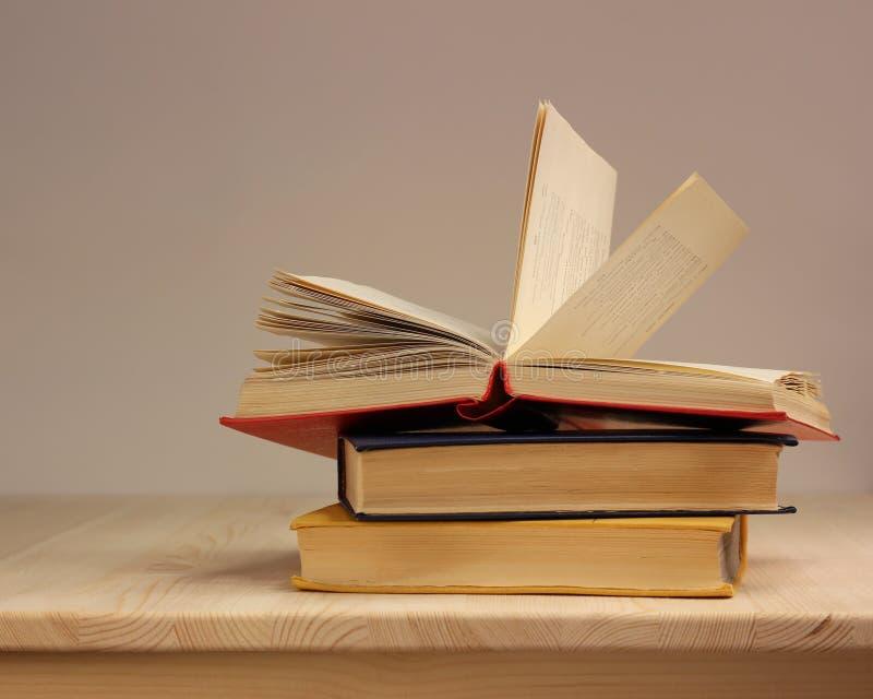 Pilha de três livros na tampa colorida na tabela imagens de stock