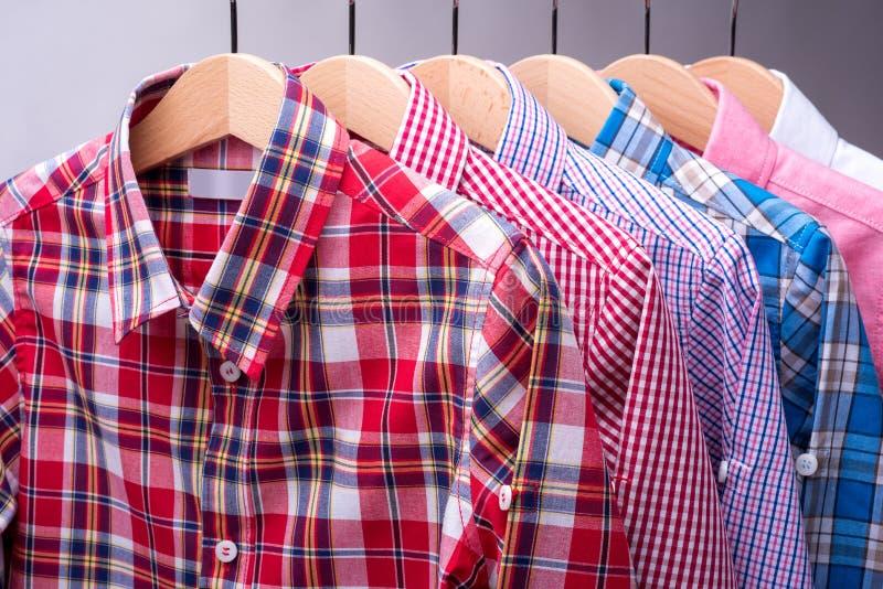 Pilha de várias camisas do ` s dos homens da manta no fundo cinzento foto de stock