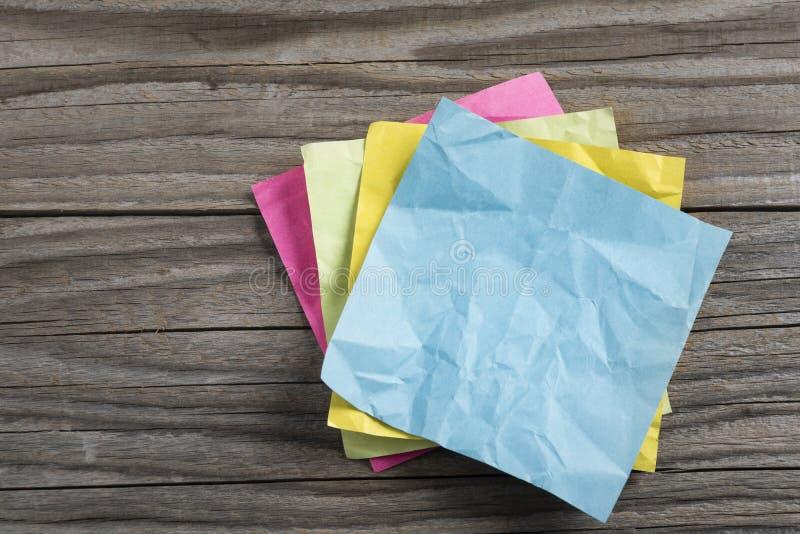 Pilha de vários multi papéis de nota coloridos amarrotados em uma superfície de madeira velha, fim acima imagem de stock