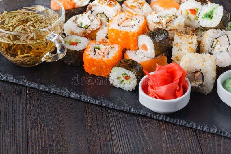 A pilha de vários tipos do sushi serviu na pedra preta imagens de stock royalty free