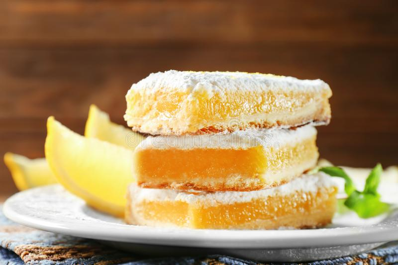 Pilha deliciosa das barras da torta do limão no fundo de madeira imagem de stock royalty free