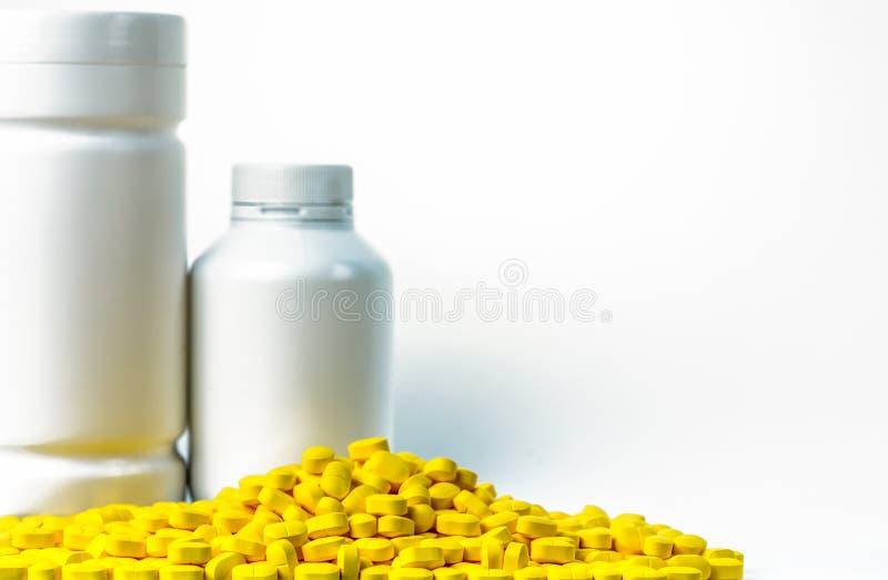A pilha do amarelo marca comprimidos perto da garrafa de comprimidos plástica com blan fotos de stock