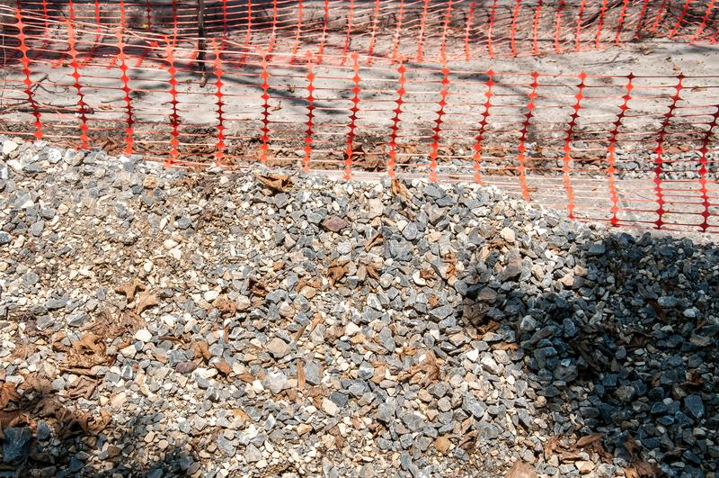 Pilha do cascalho no canteiro de obras da rua com o ascendente próximo alaranjado da rede ou da cerca de segurança imagens de stock