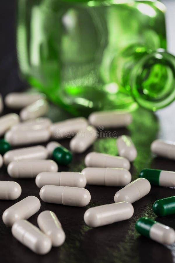 Pilha do close-up de comprimidos médicos da cor branca na garrafa médica do vintage do fundo feita do vidro verde fotografia de stock
