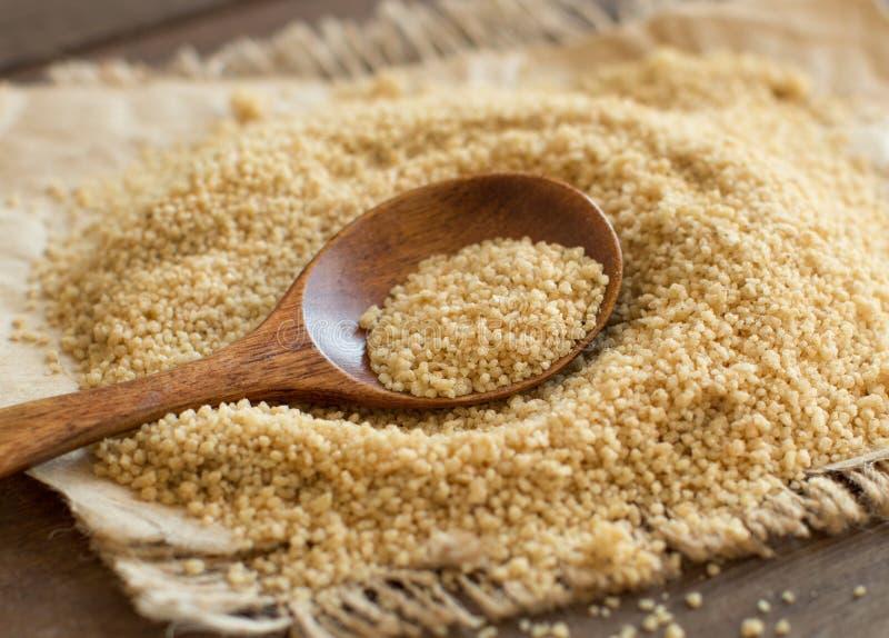 Pilha do cuscuz inteiro do trigo com uma colher fotos de stock