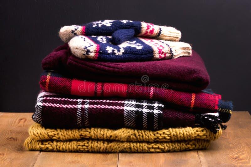 A pilha do inverno morno e acolhedor e do outono veste-se em mitenes de madeira do lenço dos casacos de lã das camisetas do fundo fotos de stock royalty free