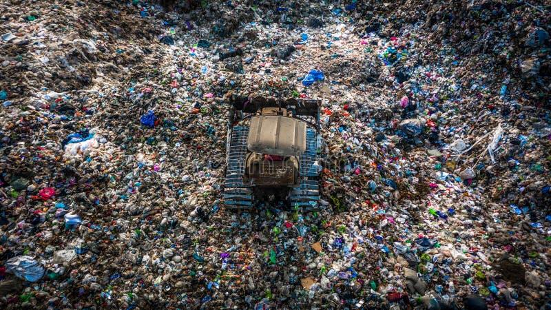 A pilha do lixo na descarga ou na operação de descarga de lixo, caminhões de lixo da vista aérea descarrega o lixo a uma operação imagens de stock royalty free