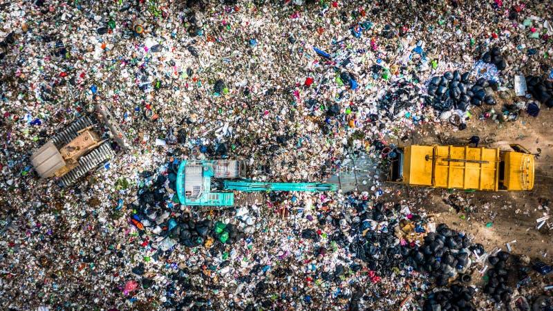 A pilha do lixo na descarga ou na operação de descarga de lixo, caminhões de lixo da vista aérea descarrega o lixo a uma operação fotos de stock