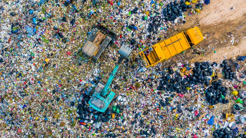 A pilha do lixo na descarga ou na operação de descarga de lixo, caminhões de lixo da vista aérea descarrega o lixo a uma operação fotografia de stock royalty free