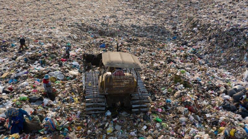 A pilha do lixo na descarga ou na operação de descarga de lixo, caminhões de lixo da vista aérea descarrega o lixo a uma operação foto de stock
