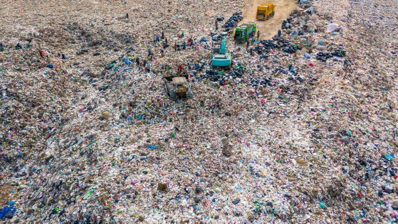 A pilha do lixo na descarga ou na operação de descarga de lixo, caminhões de lixo da vista aérea descarrega o lixo a uma operação imagens de stock