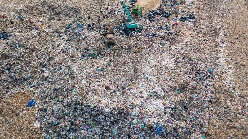 A pilha do lixo na descarga ou na operação de descarga de lixo, caminhões de lixo da vista aérea descarrega o lixo a uma operação fotos de stock royalty free