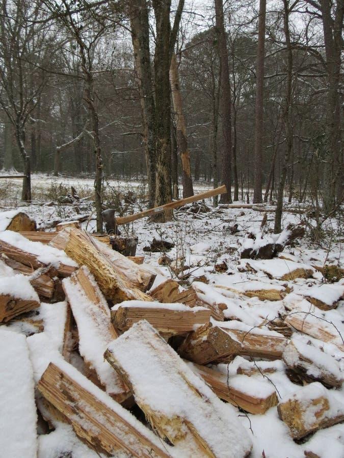 Pilha do machado e da lenha na neve dos invernos fotografia de stock