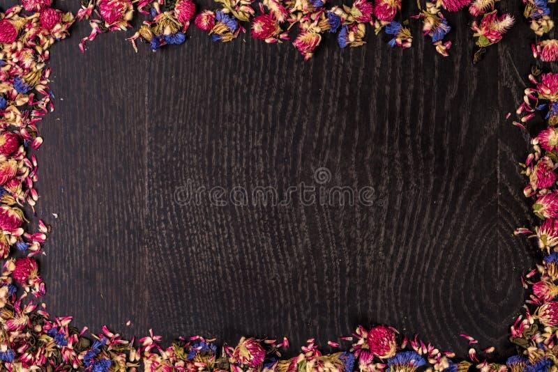 A pilha do rosa secou rosas no fundo de madeira preto como a beira imagens de stock royalty free